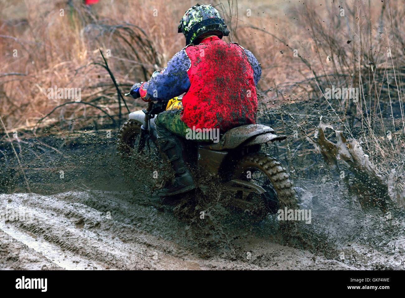 Motocross racer in fase di accelerazione in pista sterrata, vista dal retro Immagini Stock