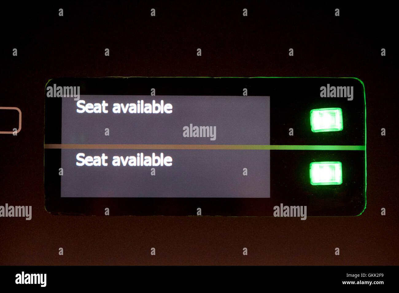 Sedile disponibile segni sul tettuccio di prenotazione del posto di schermi su un treno Immagini Stock