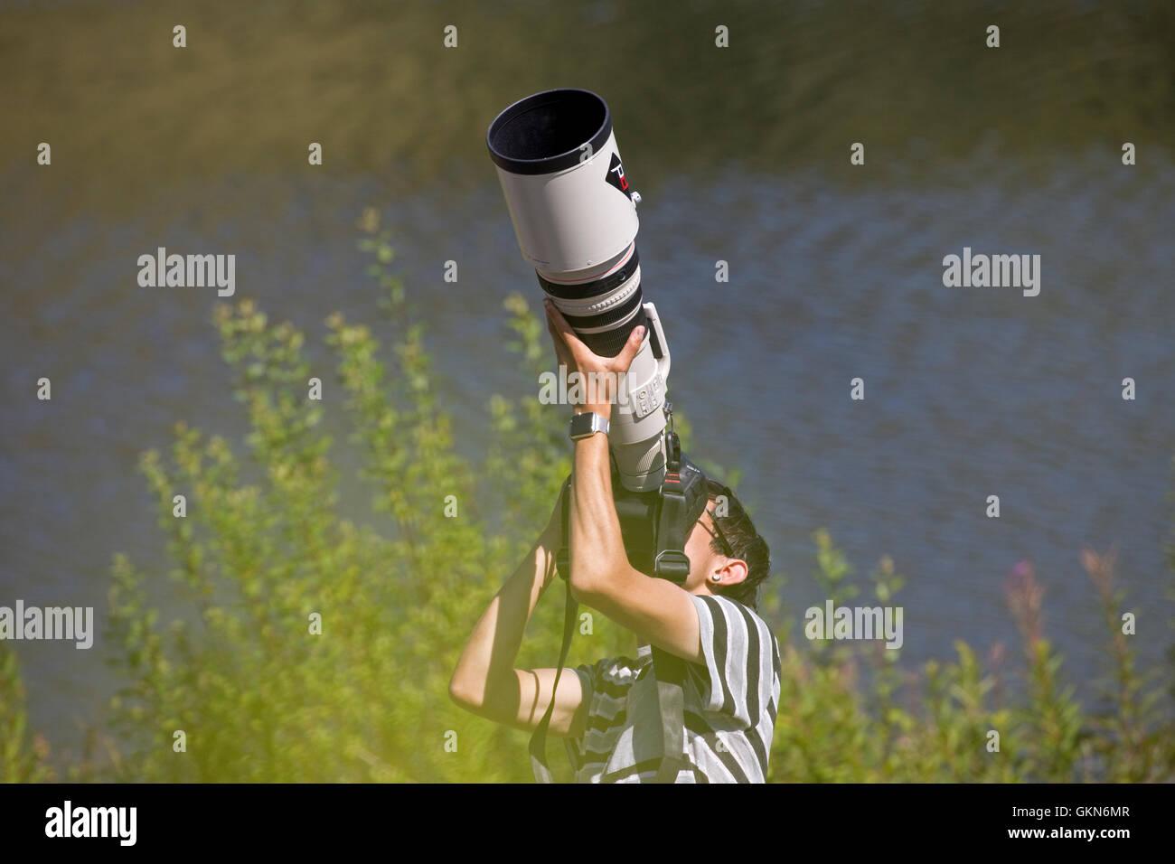 Uomo di fotografare gli uccelli big 500mm Canon teleobiettivo Bwlch Nant Yr Arian Visitor Center Ceredigion il Galles Immagini Stock