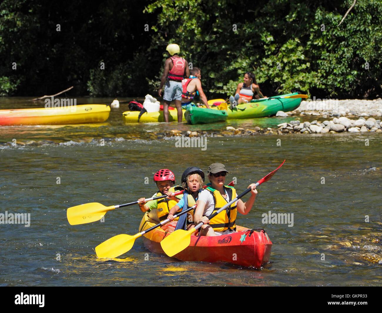 Madre con figli piccoli andando su una canoa avventura sul fiume Herault nella regione di Cevennes, Francia meridionale Immagini Stock