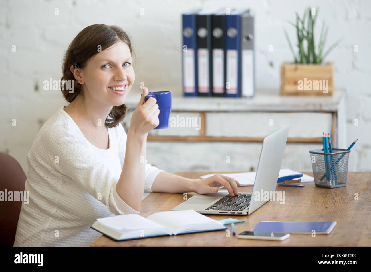 Ritratto di giovane donna d'affari di bere il caffè e utilizzando laptop in casa ufficio interno. Felice Immagini Stock