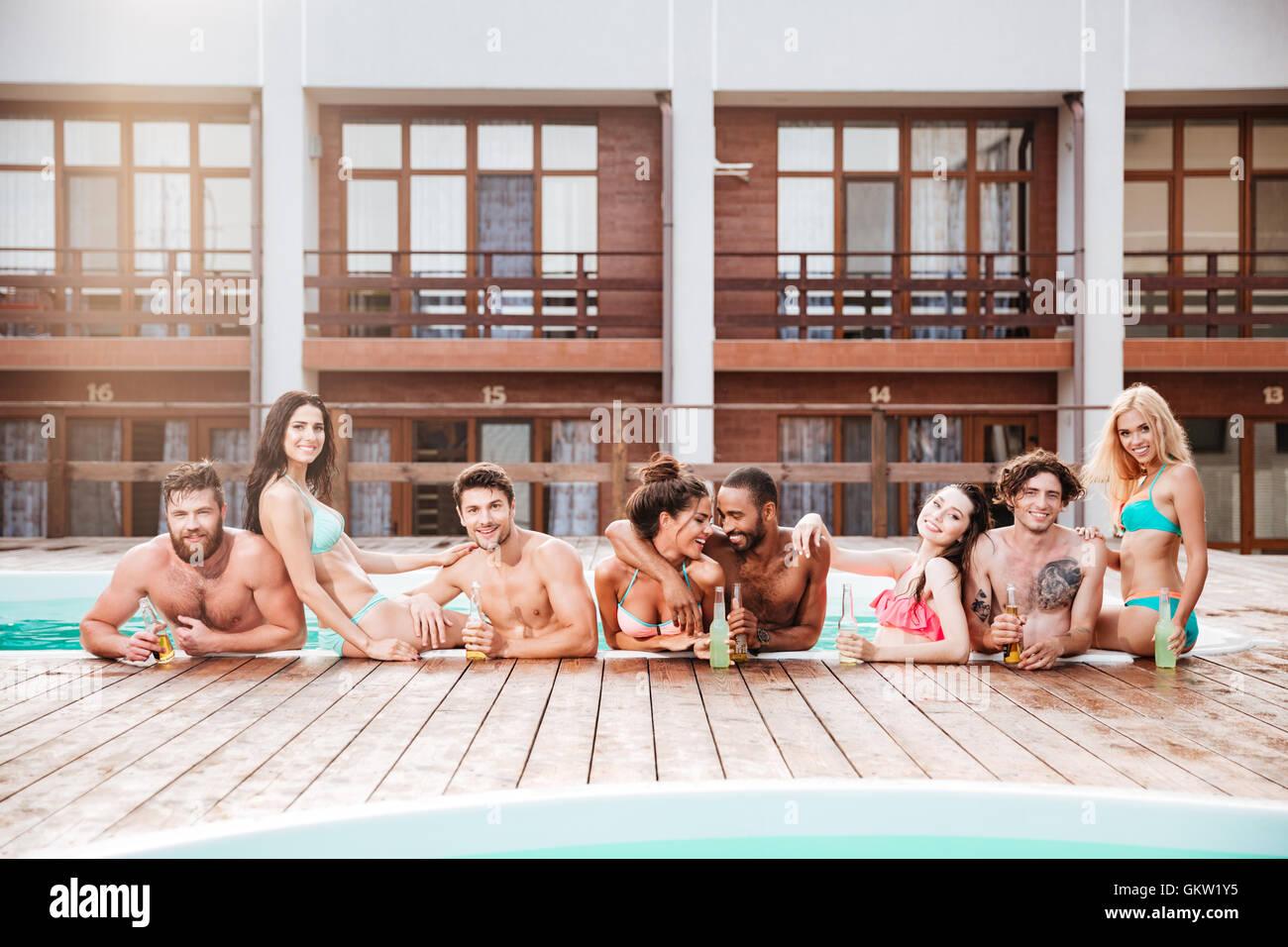 Groppa di allegro felice gli amici a bere la birra presso la piscina all'aperto Immagini Stock