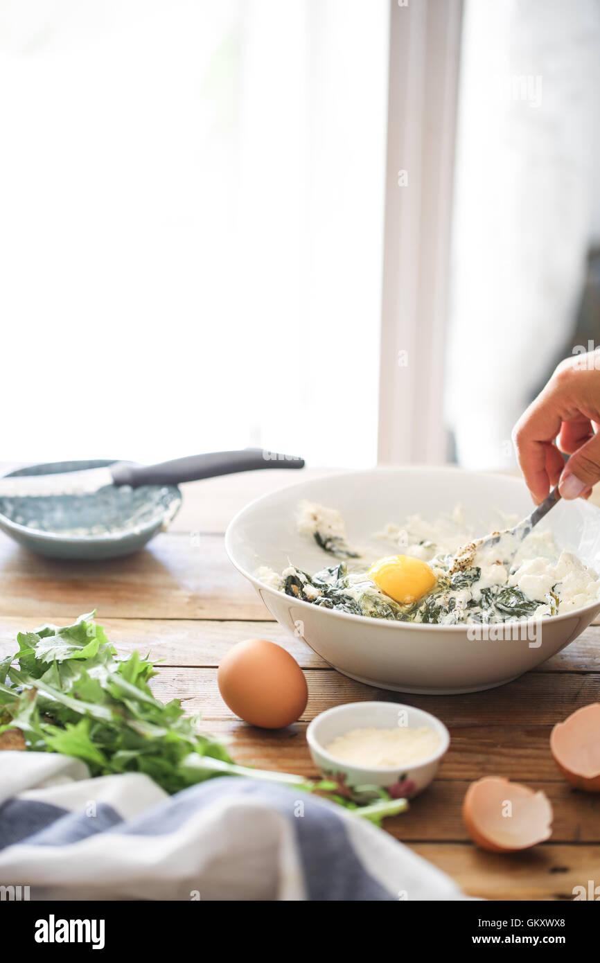 Una donna frusta gli ingredienti in una ciotola per preparare in casa le erbe tart Immagini Stock