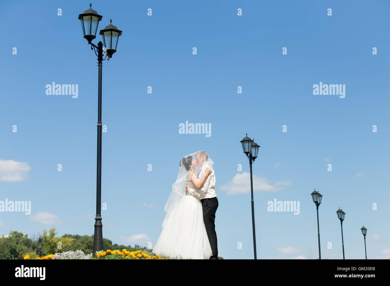 Giovani caucasici di nozze giovane kissing holding velo su capi. Bella sposa felice abbracciando e baciando lo sposo Immagini Stock
