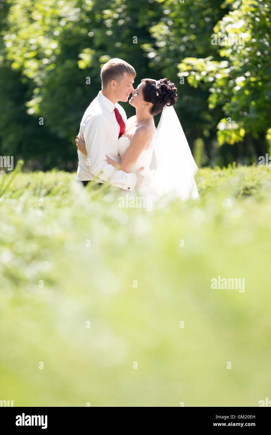 Giovani caucasici di nozze giovane kissing all'esterno. Bella sposi novelli abbracciando e baciando il giorno Immagini Stock