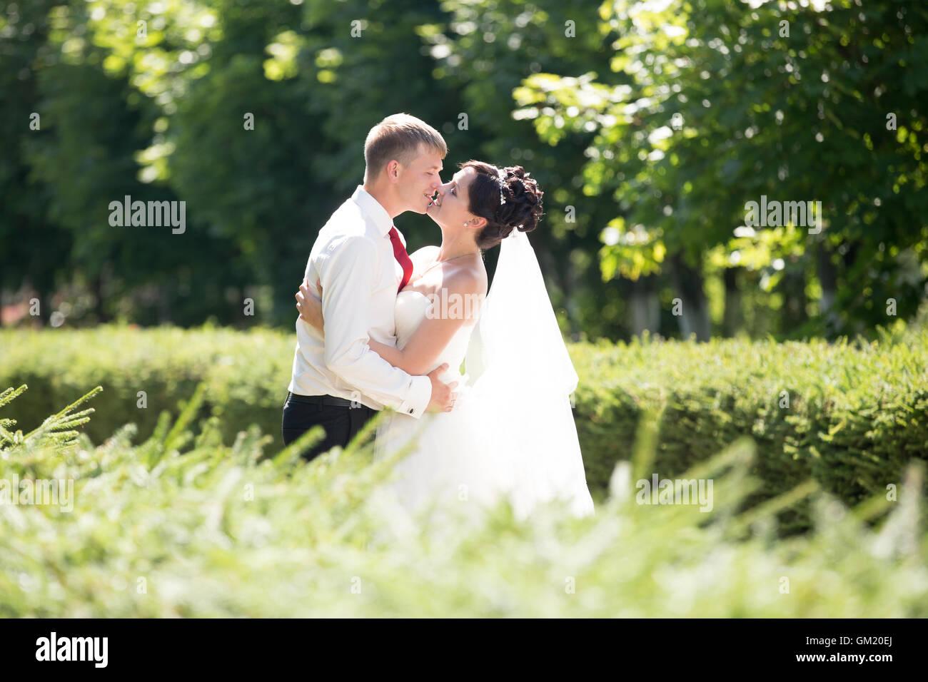 Giovani caucasici di nozze giovane kissing all'esterno. Bella sposi circa a baciare il giorno delle nozze in Immagini Stock