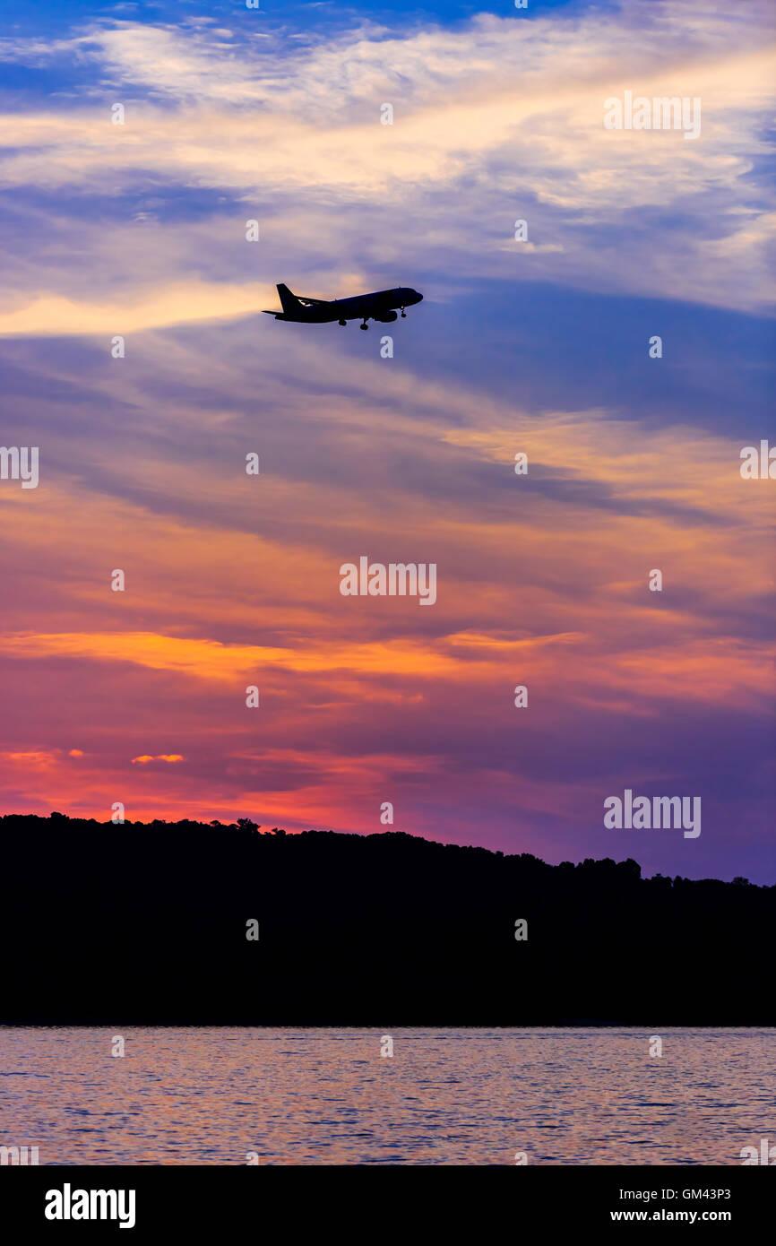 Silhouette di un aereo passeggeri sbarco al tramonto sul mare Immagini Stock