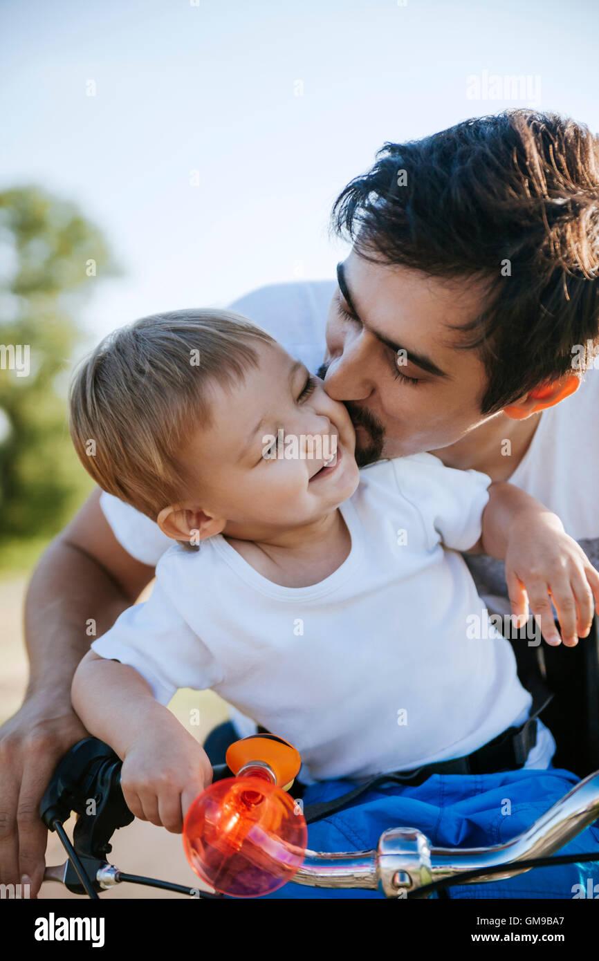 Padre baciare il suo piccolo figlio sul tour in bicicletta Immagini Stock