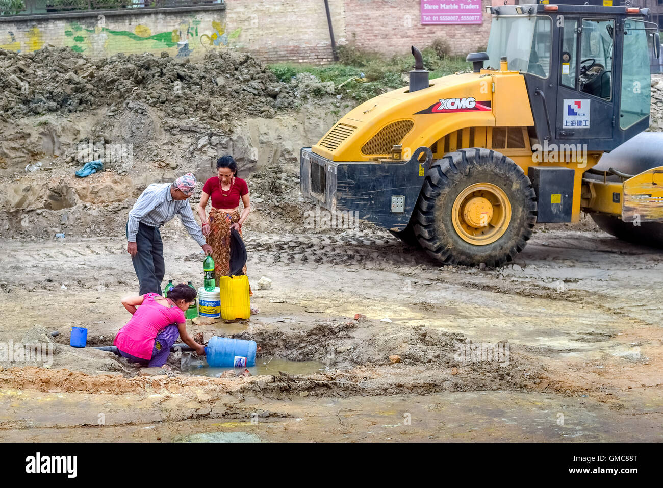 Una famiglia locale di raccolta di acqua da un tubo rotto in Kathmandu, Nepal. © Rinaldo Sumayku Immagini Stock