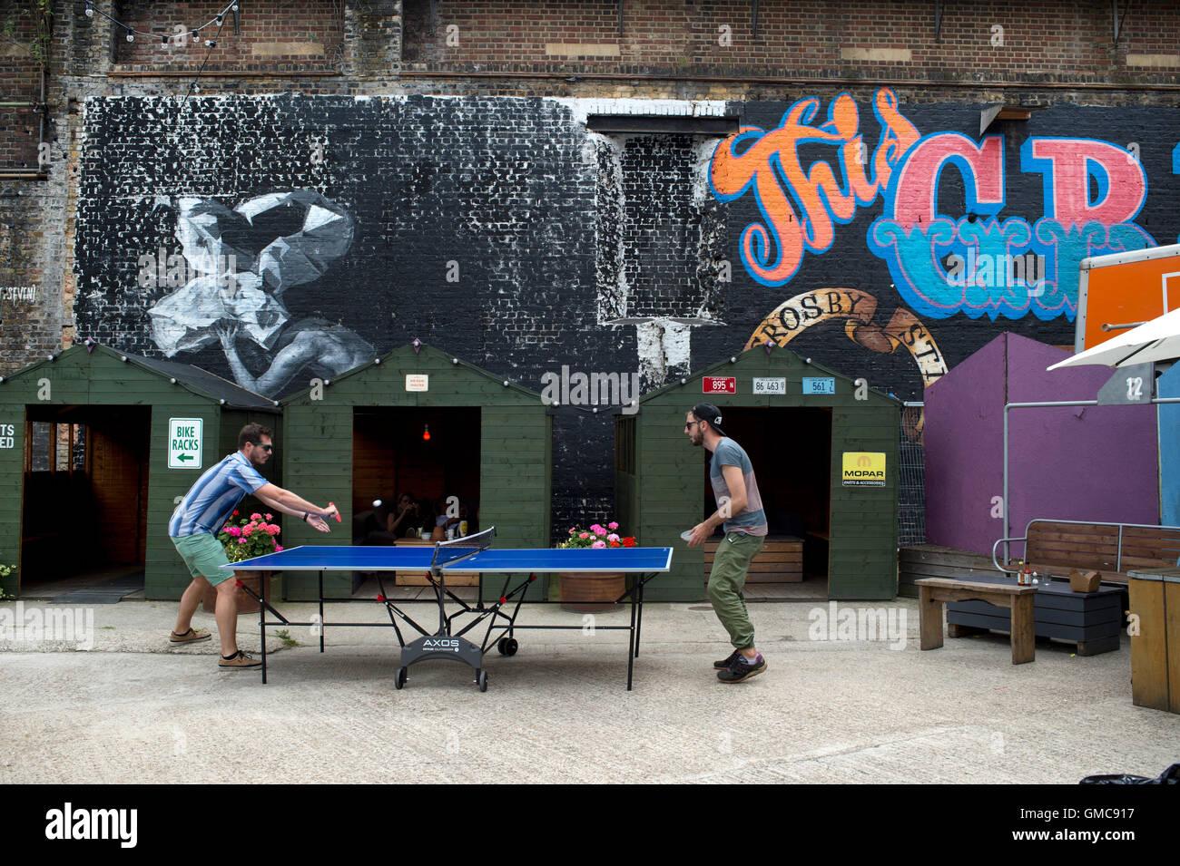 Hackney Wick. Due giovani uomini giocare a ping pong. Immagini Stock