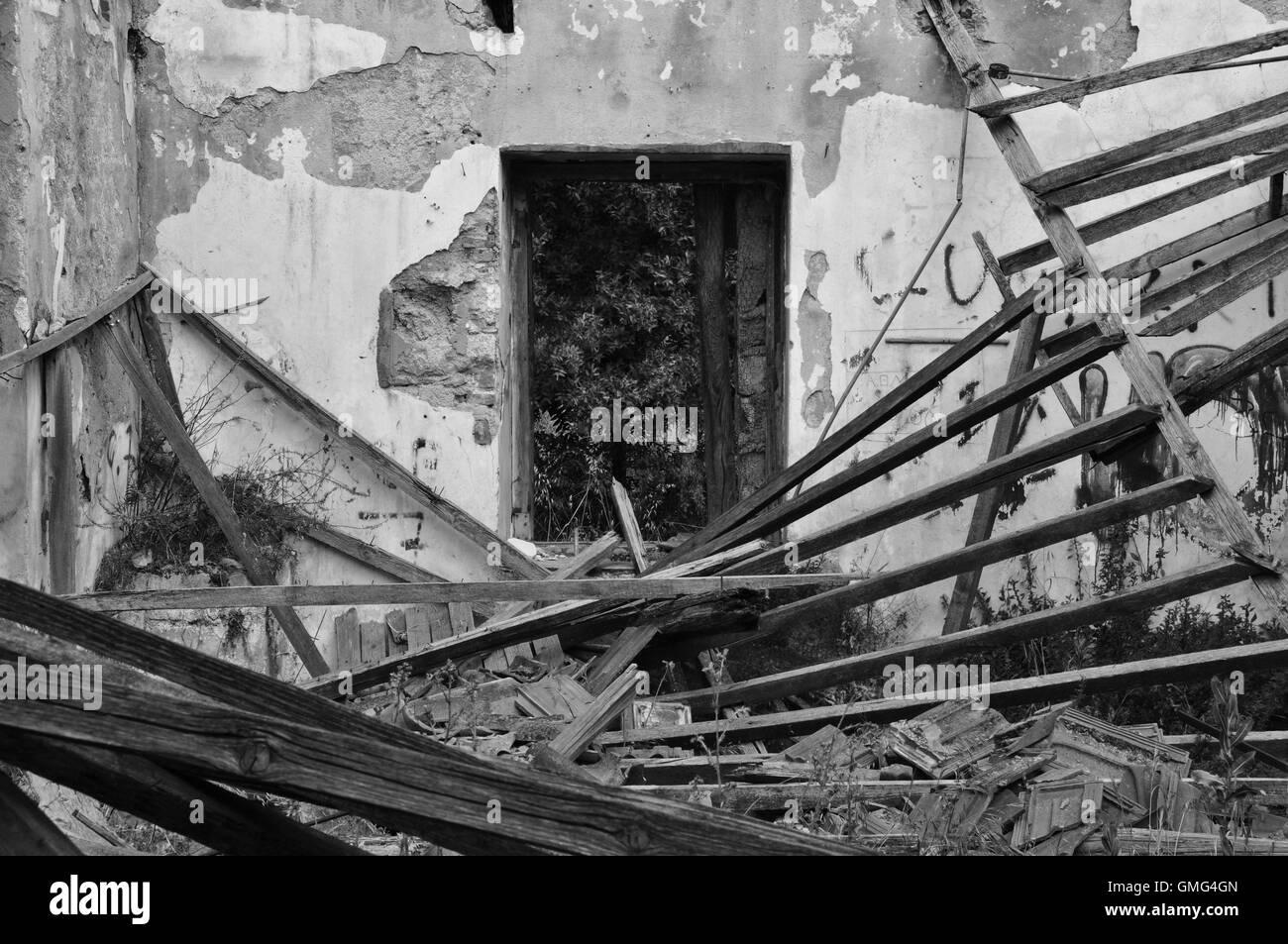 Crollo del tetto scheggiati muri interni e la finestra di una casa abbandonata. In bianco e nero. Foto Stock
