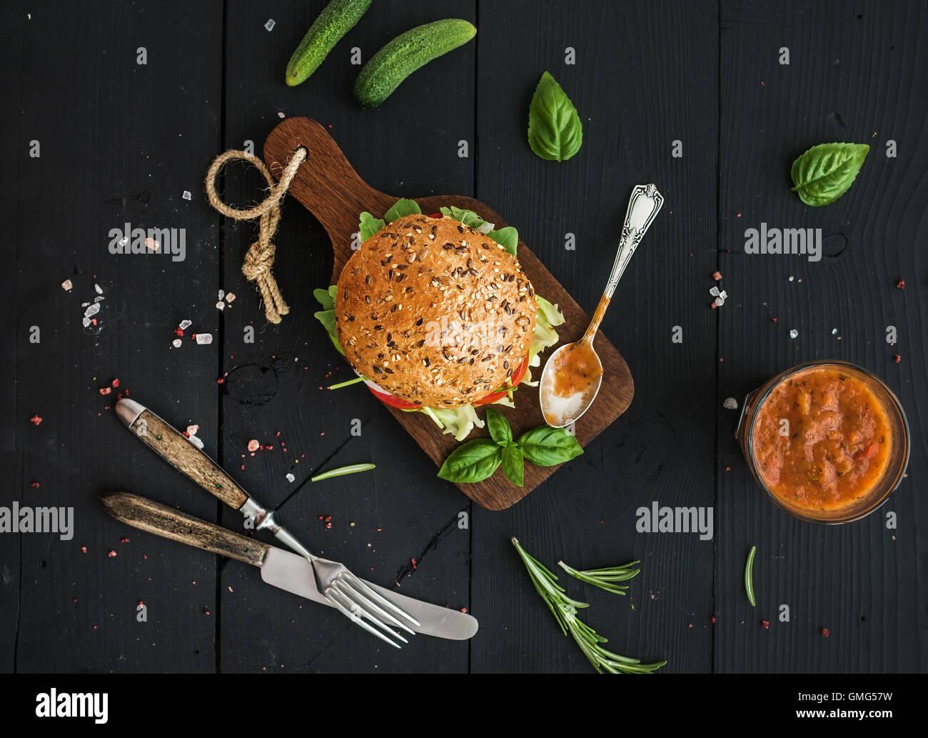 Freschi Fatti in casa burger il buio che serve board con il piccante salsa di pomodoro, sale marino Immagini Stock