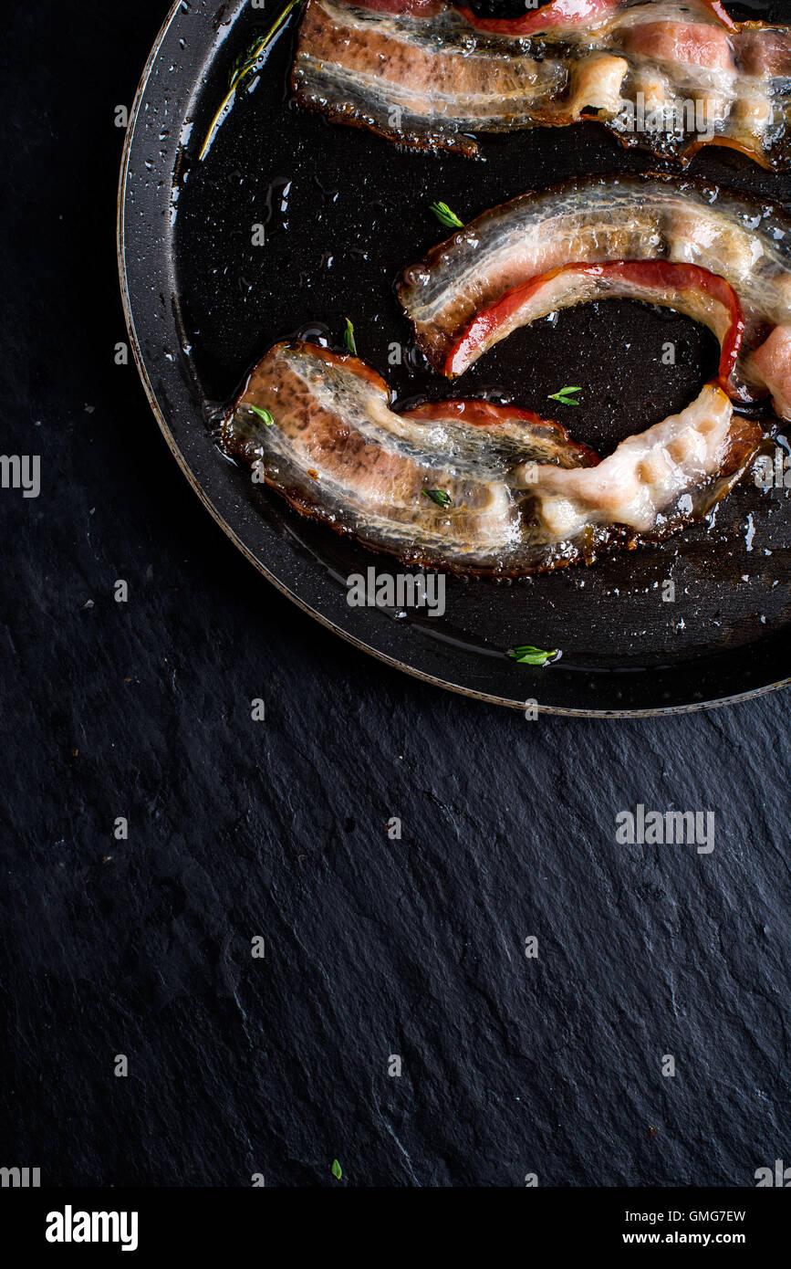 Pan di pancetta fritta su nero ardesia sfondo Immagini Stock