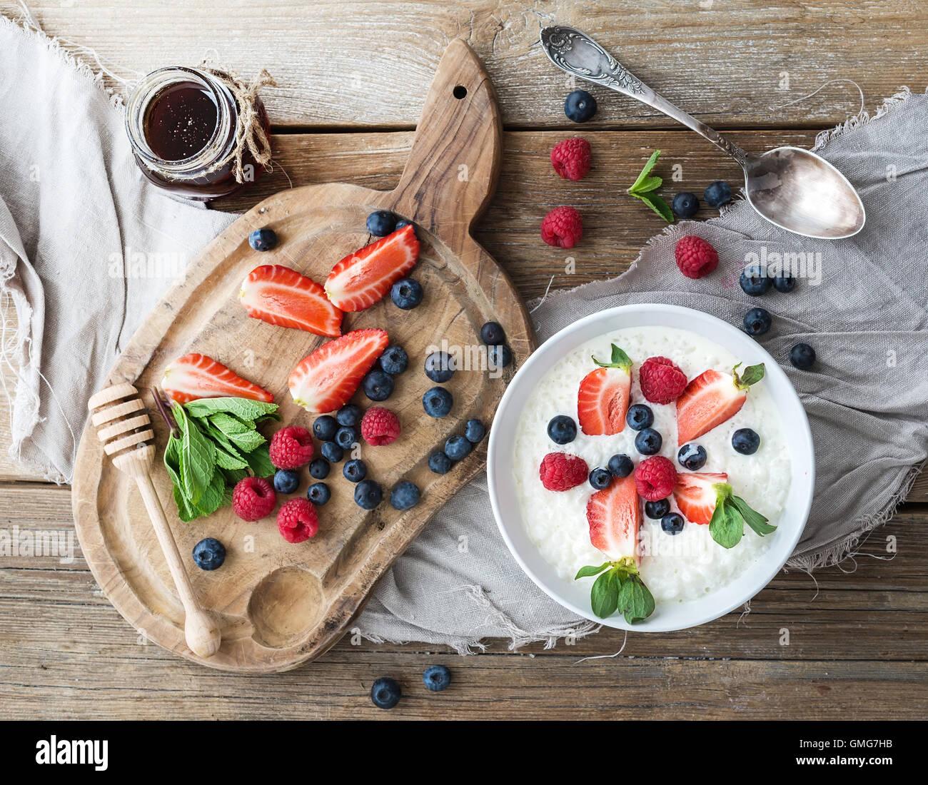 Sana colazione set. Cereali di riso o porridge con frutti di bosco e miele Immagini Stock