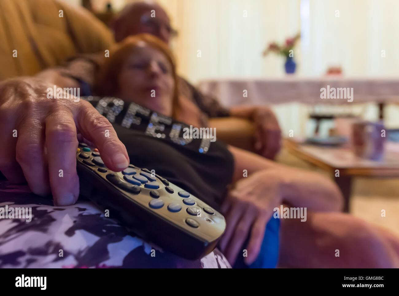 Anziana coppia anziana che si trova a casa rilassarsi su un divano in un soggiorno guardando la TV. Coronavirus COVID19 blocco pandemico. Tutti i giorni. Foto Stock
