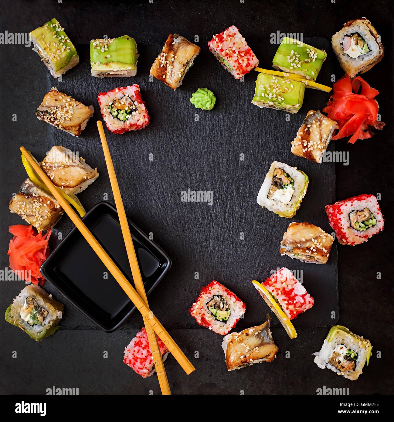 Tradizionale cibo giapponese - sushi, rotoli e salsa su uno sfondo nero. Vista superiore Immagini Stock