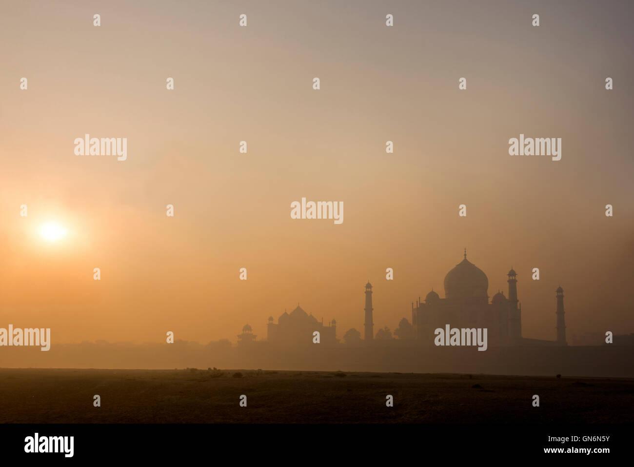 Il sole che aumenta nelle prime ore del mattino la nebbia oltre il Taj Mahal di Agra, Uttar Pradesh. India Immagini Stock