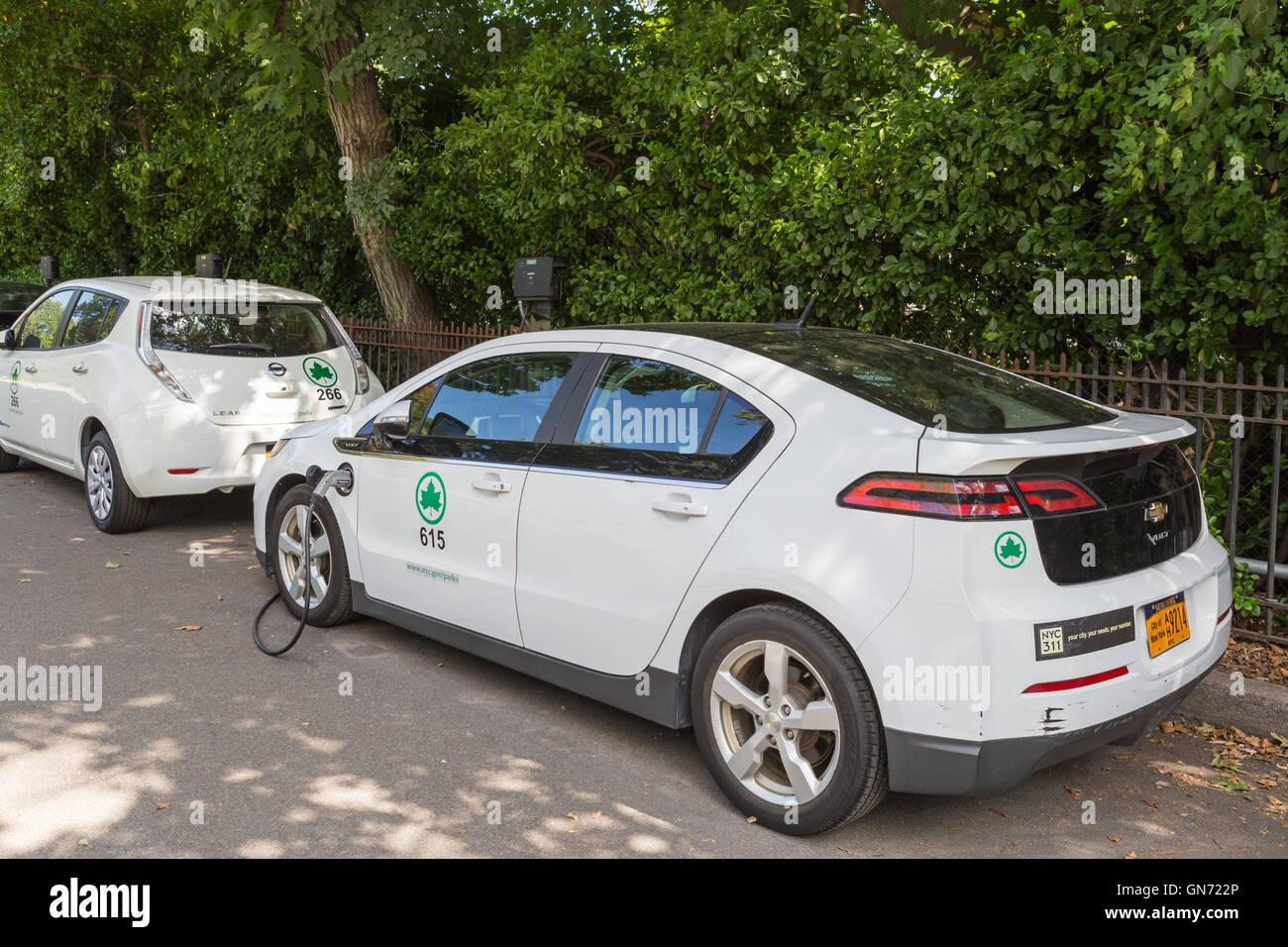 New York City Dipartimento parchi Chevy Volt e la Nissan Leaf auto elettriche ricevono una carica in corrispondenza Immagini Stock