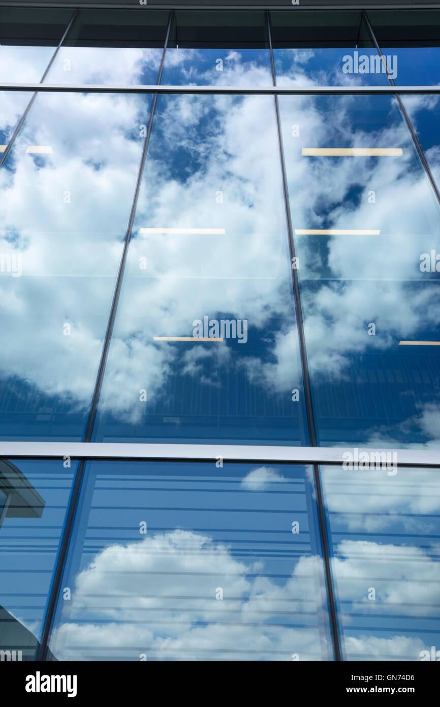 PUFFY nuvole bianche cielo blu riflessa sul vetro Edificio per uffici di Windows Foto Stock