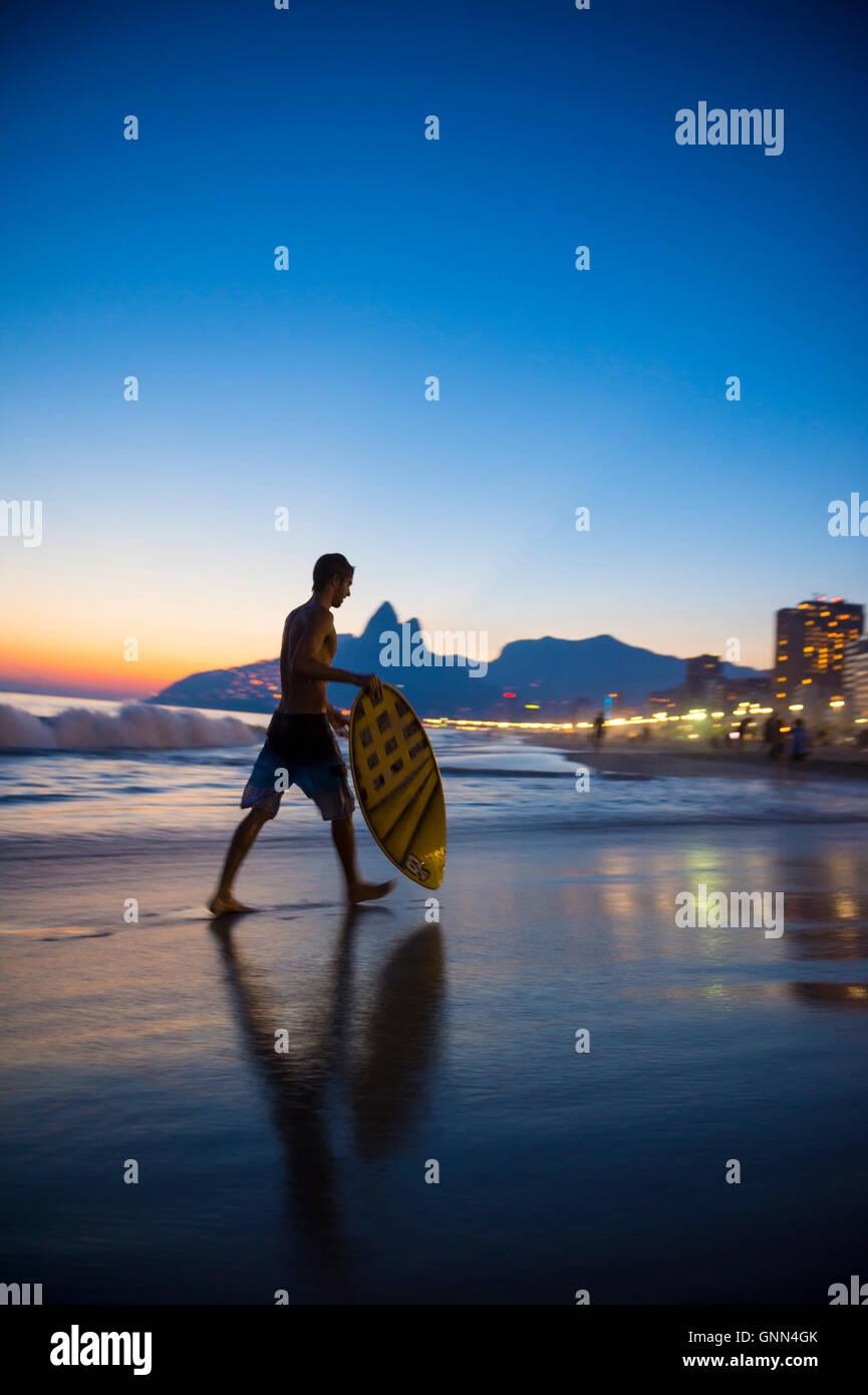 RIO DE JANEIRO - MARZO 24, 2016: Giovani carioca brasiliano indagini skimboarder il tramonto onde sulla riva della Immagini Stock