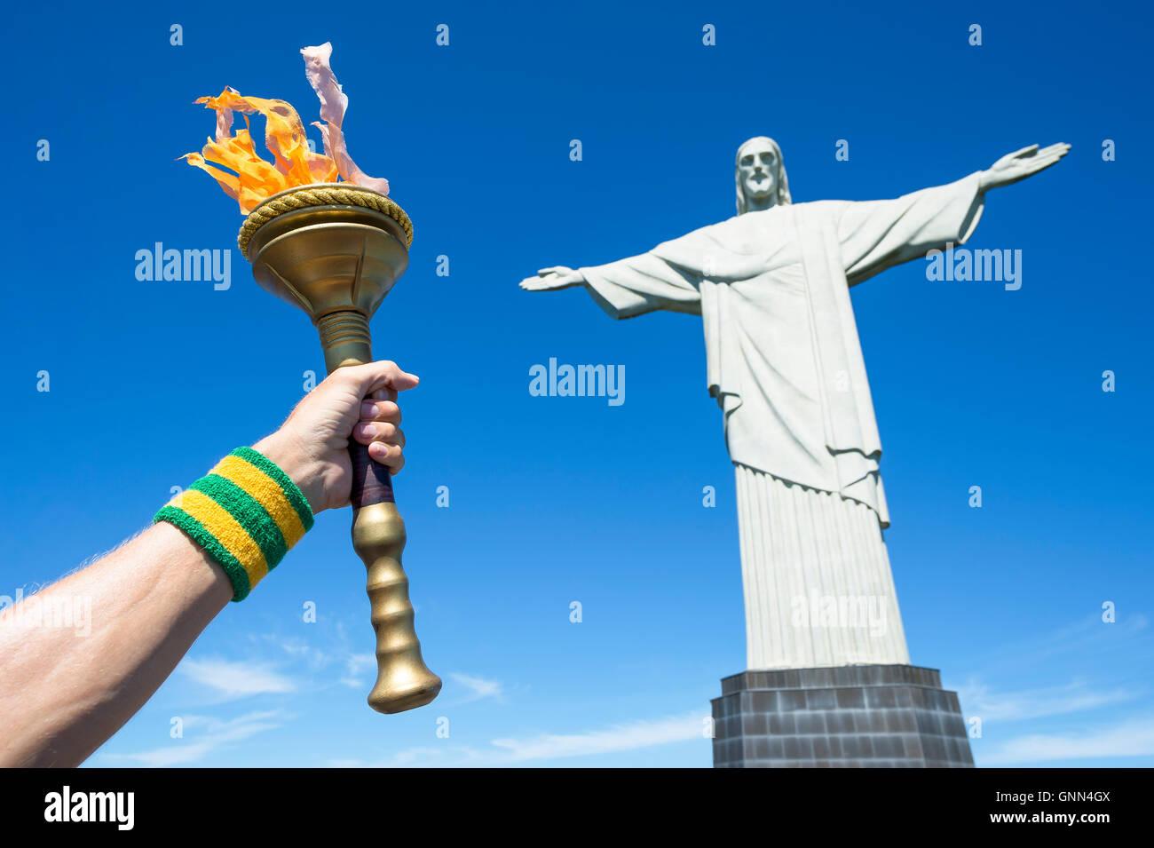 RIO DE JANEIRO - MARZO 21, 2016: Torchbearer torcia di contenimento nella parte anteriore della statua del Cristo Immagini Stock