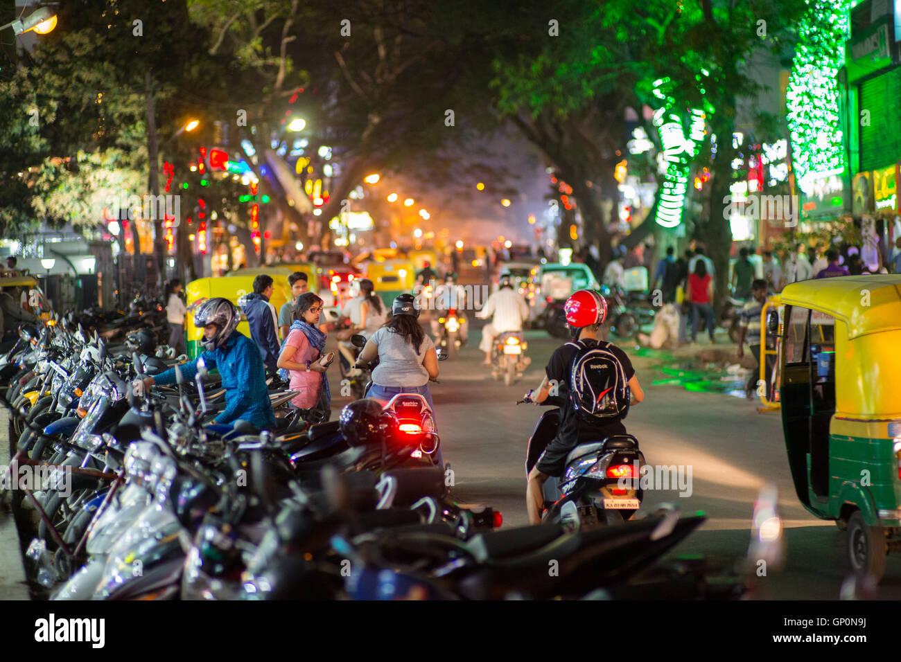 La strada è piena di gente e scooter in il partito popolare zona di notte a Bangalore in India Immagini Stock