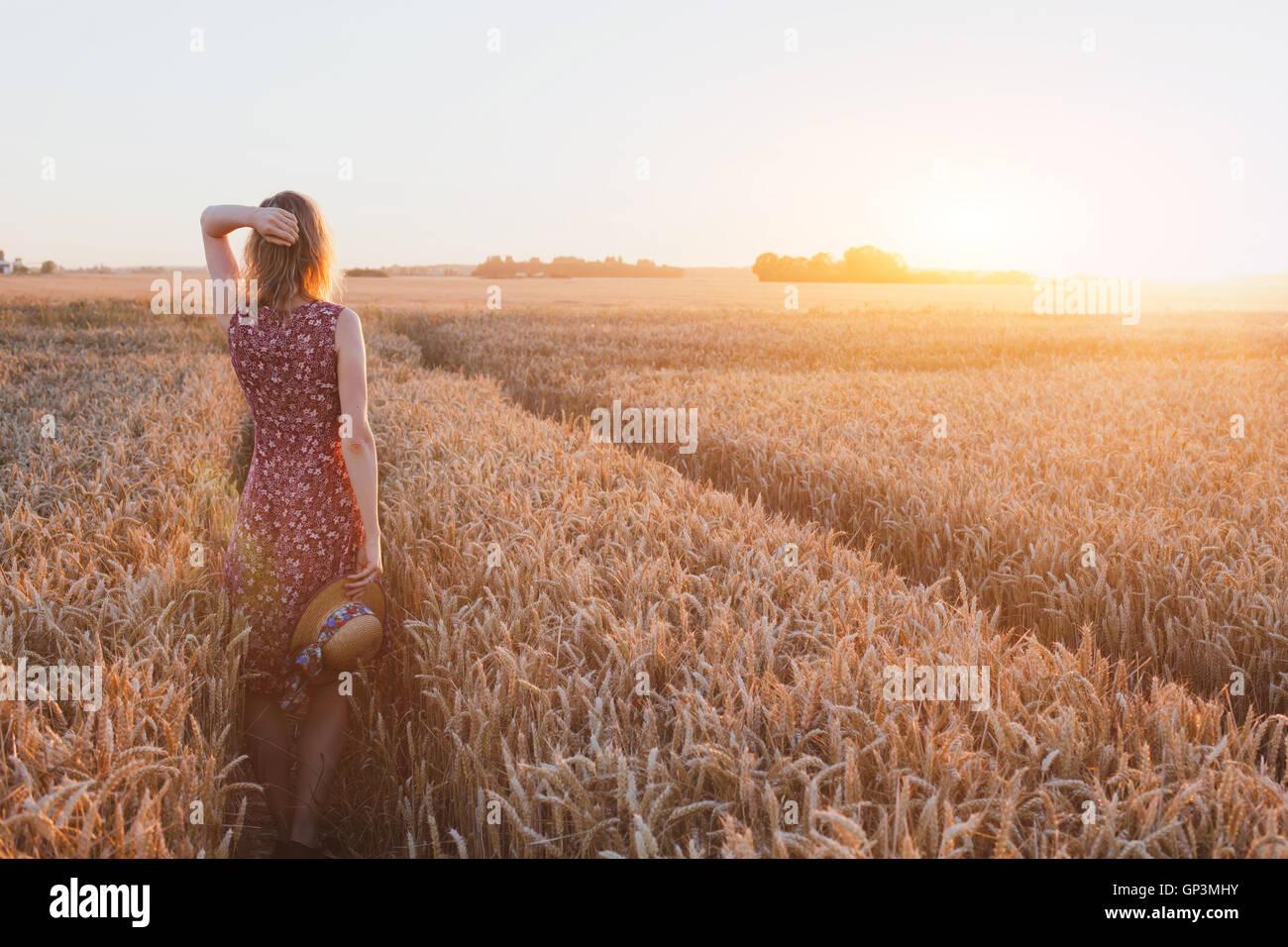 Ispirazione o il concetto di attesa, felice bella giovane donna nel campo del tramonto, sogno Immagini Stock
