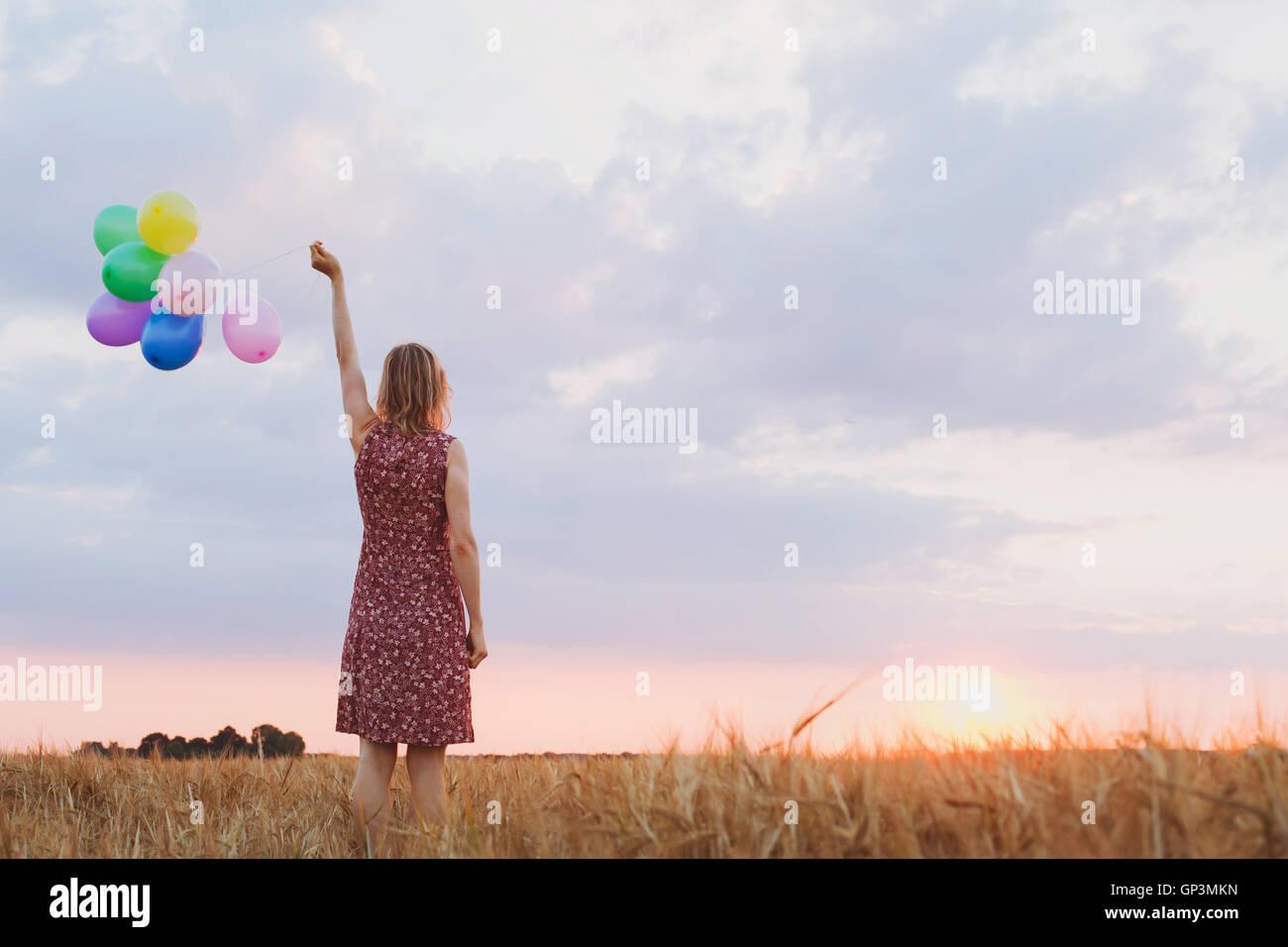 Il concetto di speranza, emozioni e sentimenti, donna con palloncini colorati nel campo, sfondo Immagini Stock