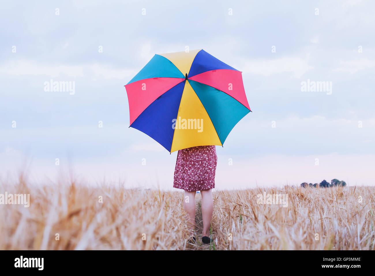 Donna con ombrello coloratissimo nel campo, ottimista positivo sfondo multicolore con copyspace Immagini Stock