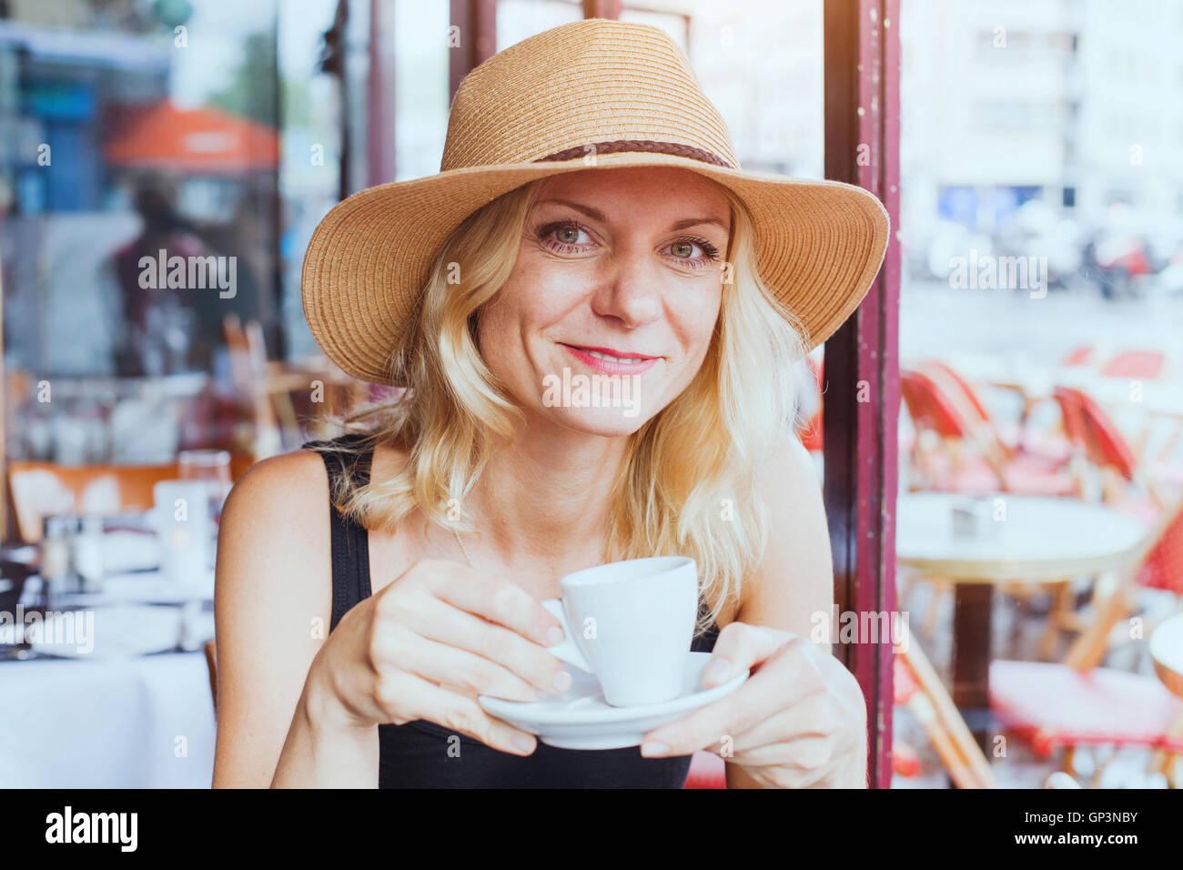Ritratto di moda bella donna di mezza età in cafe con tazza di caffè, felice e sorridente e guardando Immagini Stock