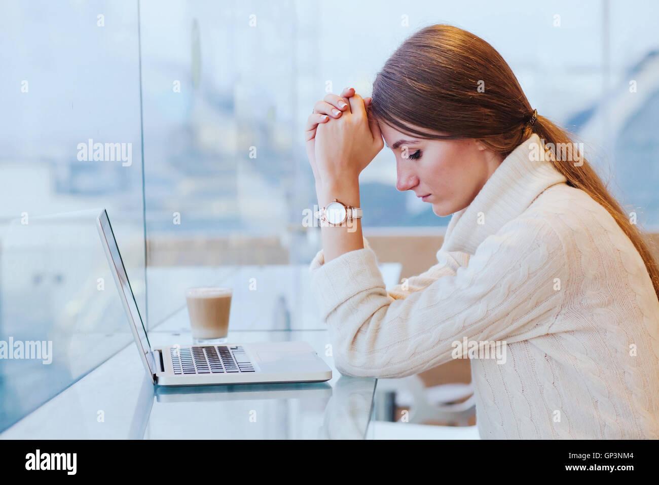 Sovraccarico di informazioni, il concetto di stress, triste disperata donna nella parte anteriore del computer Immagini Stock