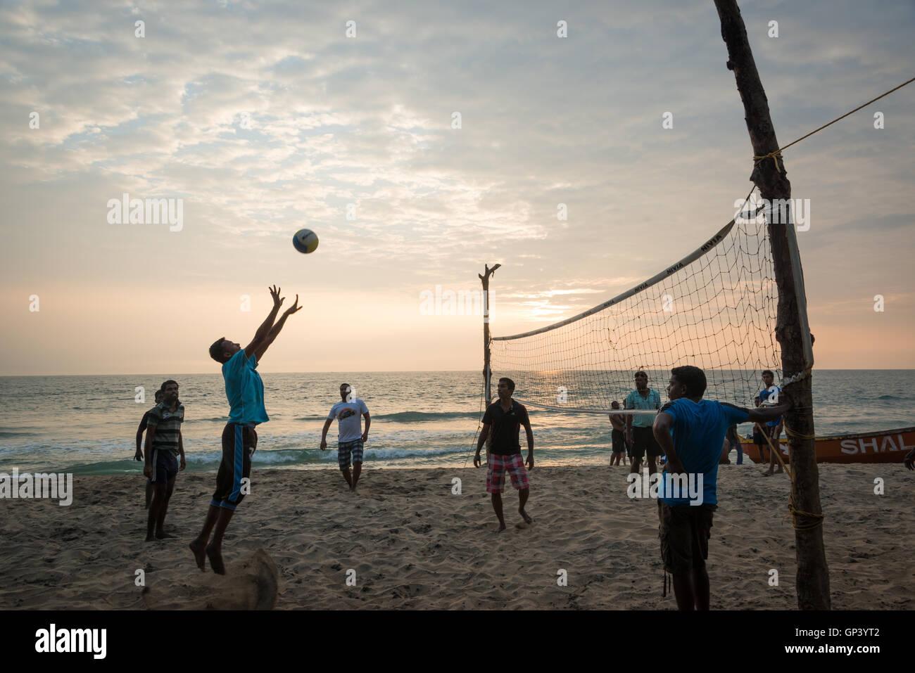 I bambini giocando a pallavolo sulla spiaggia di Varkala Kerala, India Immagini Stock