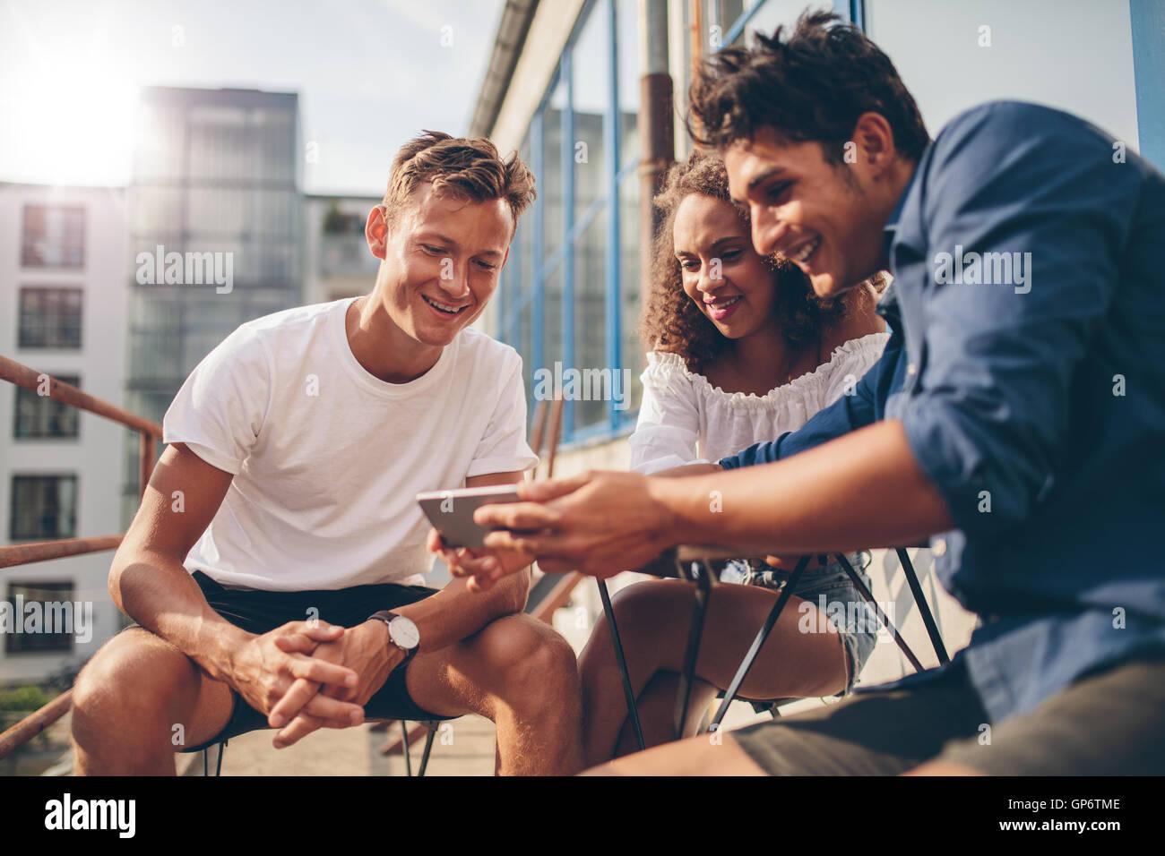 Gruppo di persone a guardare video sul telefono cellulare mentre è seduto alla outdoor cafe. Tre giovani amici Immagini Stock