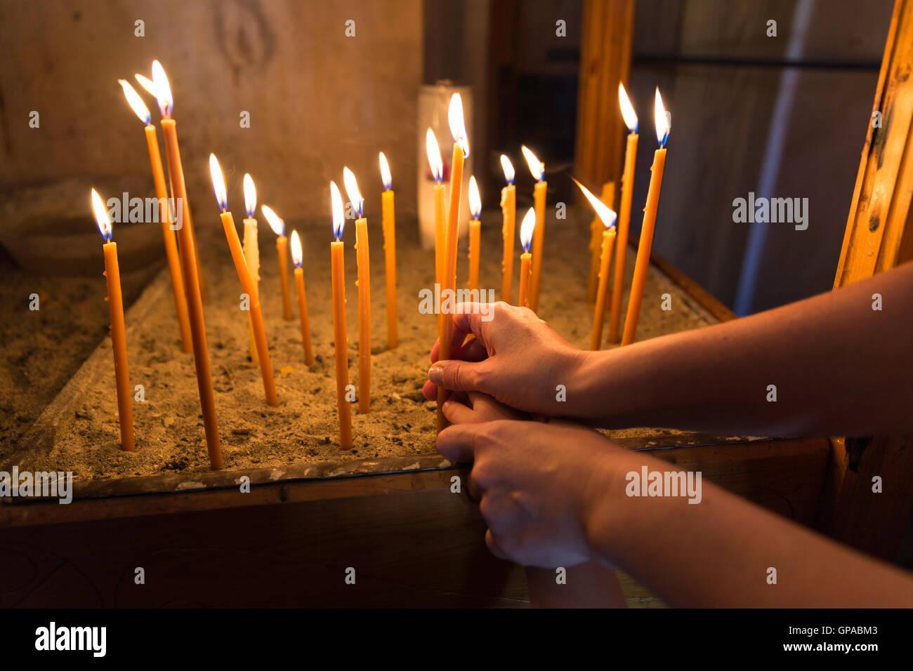 La madre e il bambino di illuminazione e tenendo un cero nella chiesa ortodossa Immagini Stock