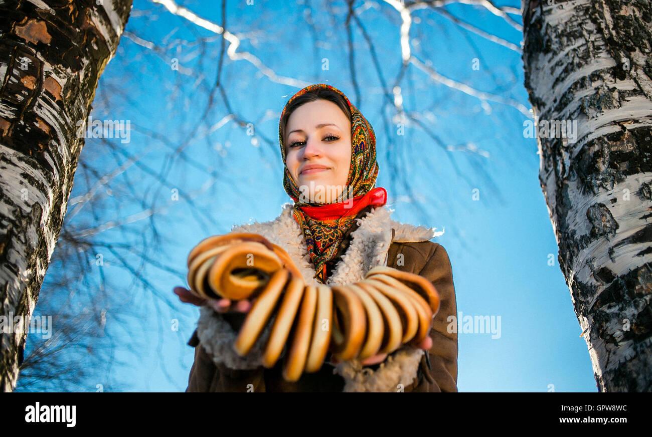 Giovane bella donna vestita in nazionale russa ha dato la suite bagel a soleggiata giornata invernale Immagini Stock