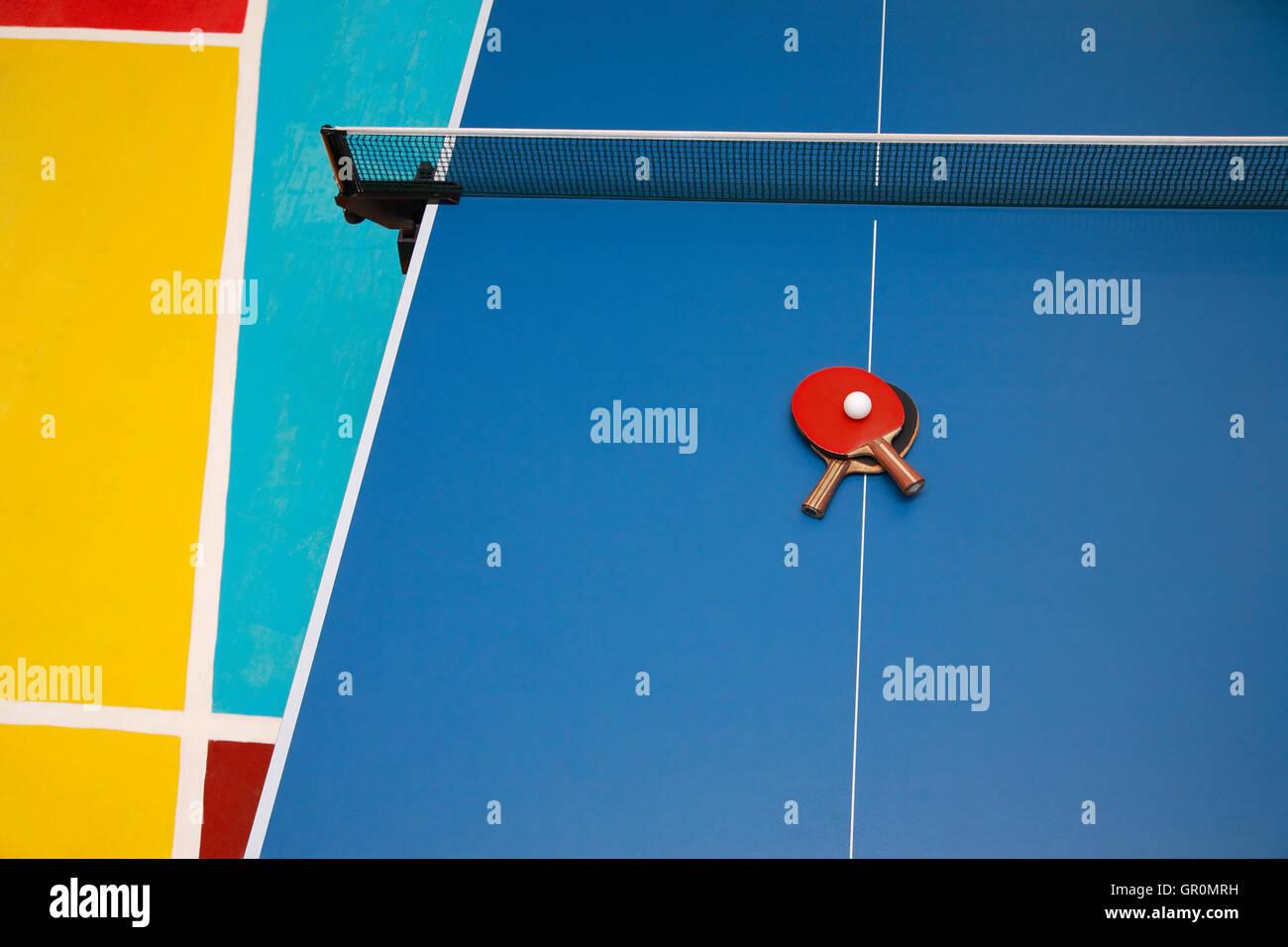 Le racchette per il blu tavolo da ping pong del rosso e del nero e del colore di una sfera su un ping pong, vista da sopra Foto Stock