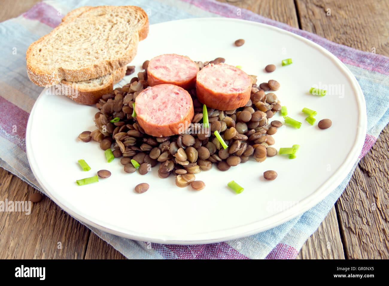 Lentil Verde con salsiccia di maiale (cotechino) sulla piastra bianca Immagini Stock