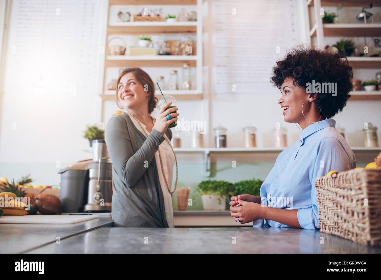 Due giovani donne juice bar dipendenti in piedi dietro il contatore. Giovani donne che lavorano al succo di frutta Immagini Stock