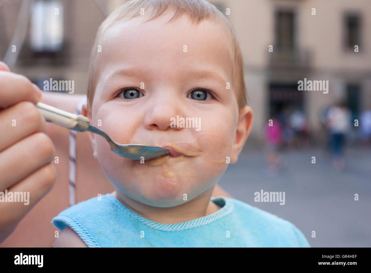 Madre che nutre il suo bambino Ragazzo con frutta poltiglia all'aperto Immagini Stock
