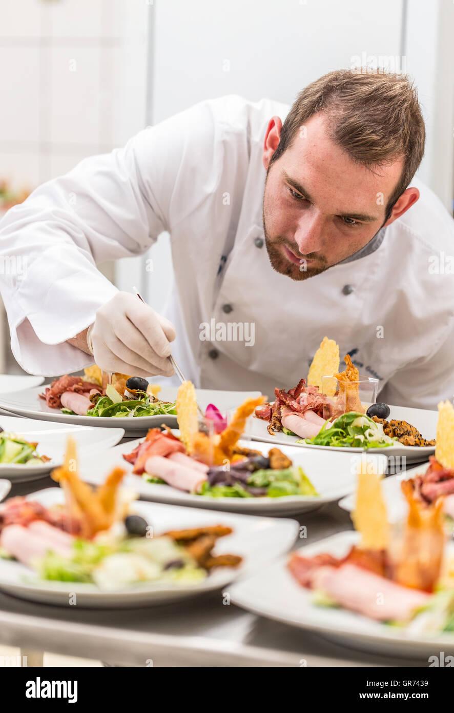 Concentrato chef maschio decorare piatto antipasto in cucina ...