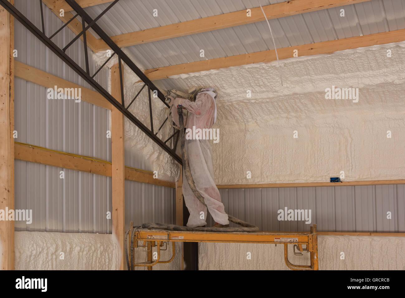 Un tecnico si applica schiuma a celle aperte in isolamento per una struttura di interni per il controllo del suono Immagini Stock