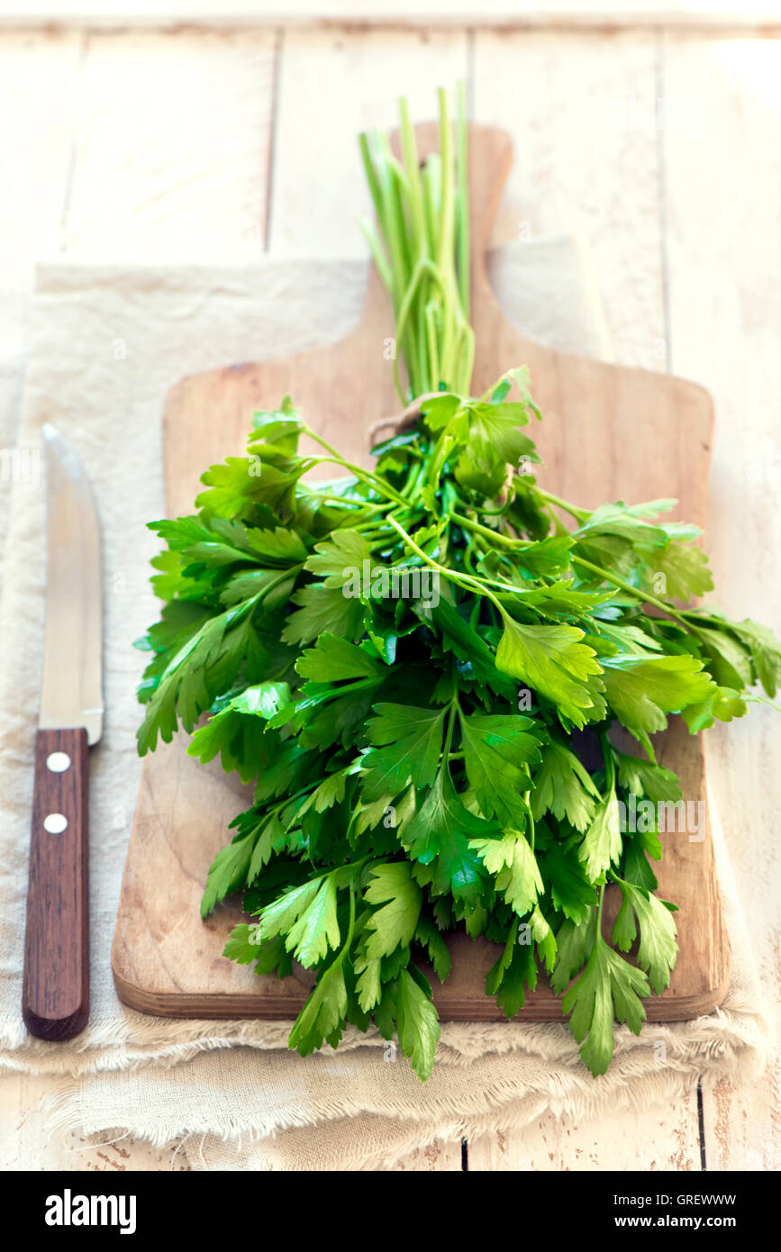 Organici di Prezzemolo italiano closeup su tavola in legno rustico, sano cibo vegetariano Immagini Stock