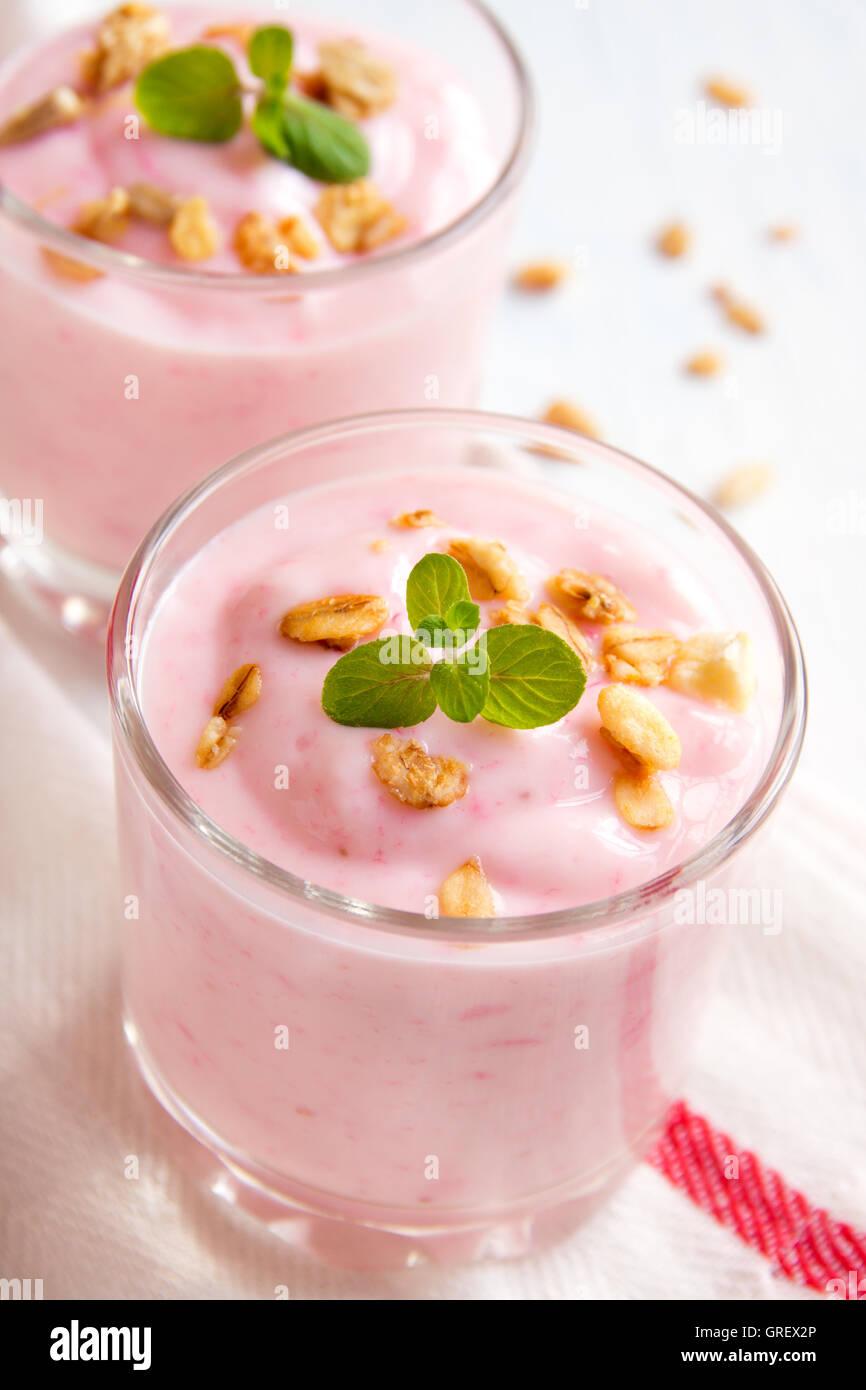Organico casalinga di yogurt alla fragola con granola e menta nella porzione bicchieri close up Immagini Stock