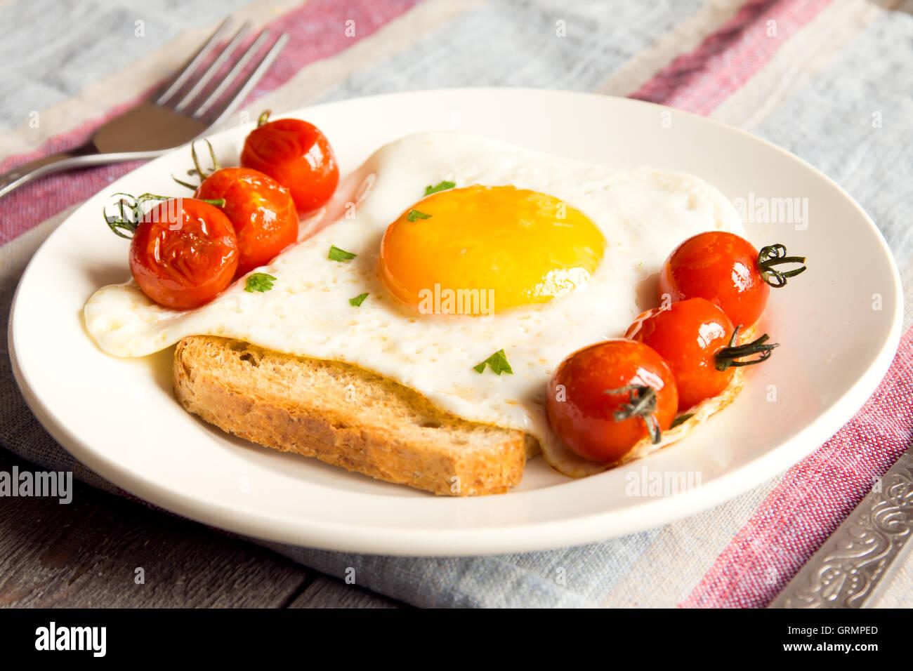 Uovo fritto sul pane e pomodori fritti per la colazione sulla piastra e tavolo rustico Immagini Stock