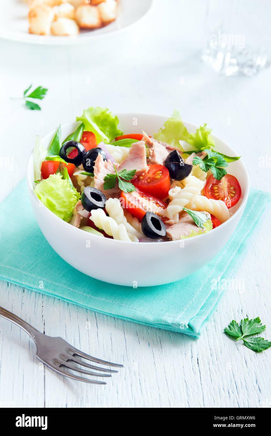 Tonno e insalata di pasta con pomodori freschi, olive, erbe aromatiche in vaso bianco su sfondo di legno Immagini Stock