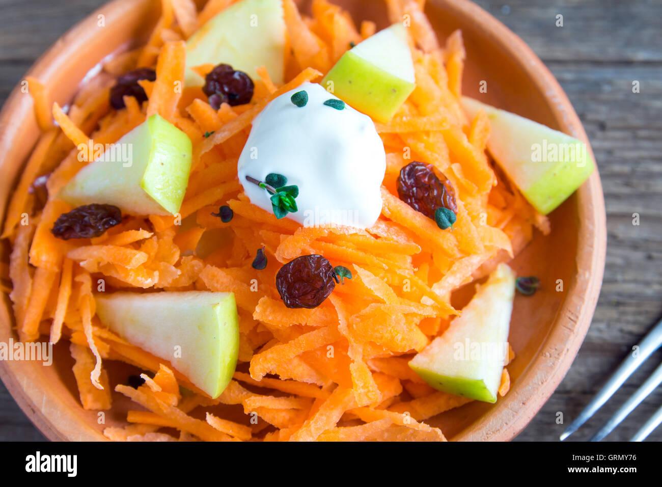 Carote e insalata di apple con uvetta, lo yogurt e le erbe in un rustico vaso di ceramica close up Immagini Stock