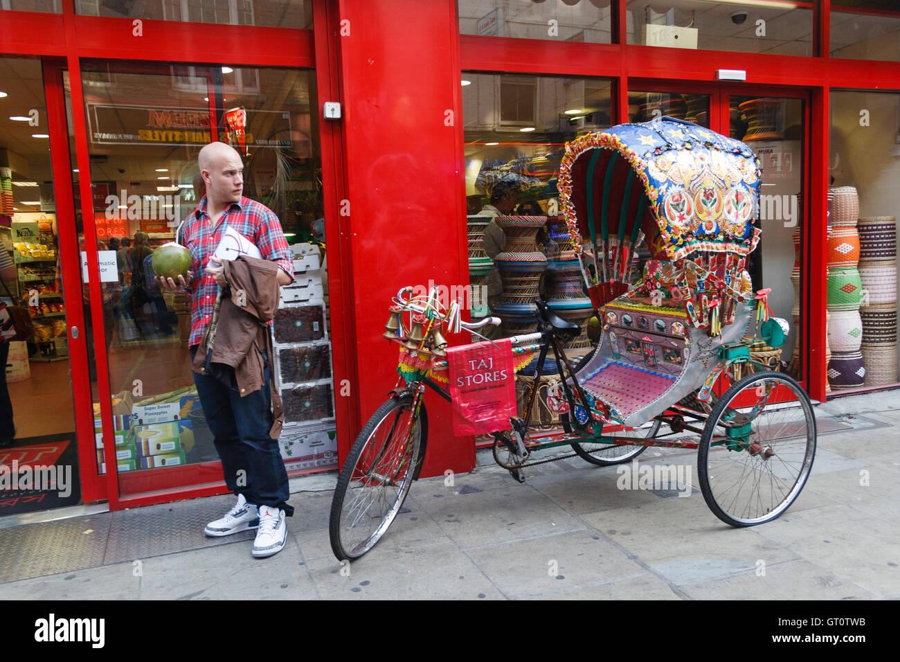 Uomo in piedi accanto al colorato di risciò bengalese, Brick Lane, Londra, Regno Unito. Foto Stock