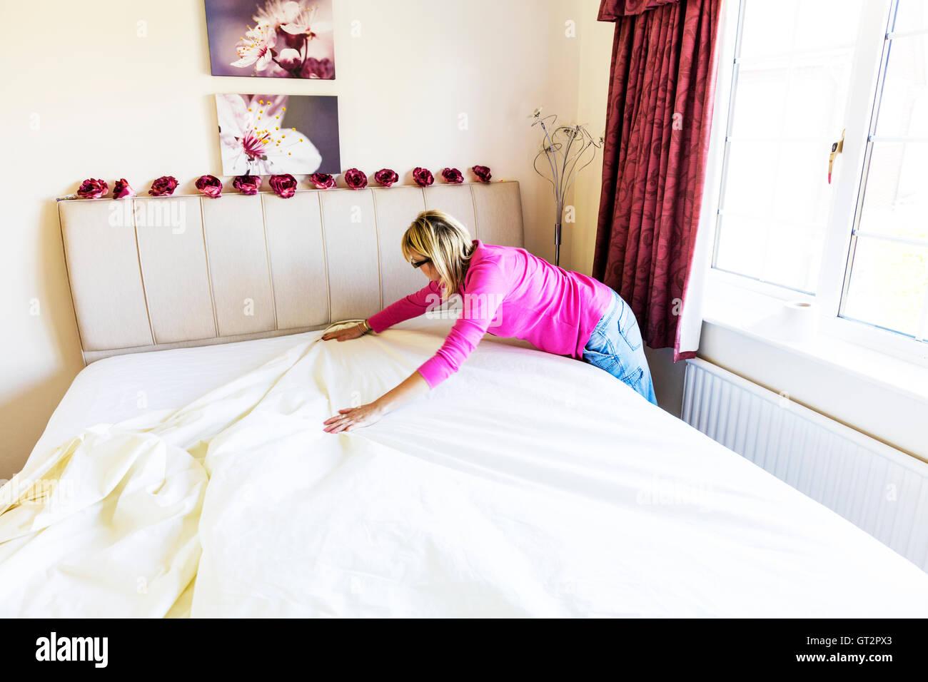 Fare il letto facendo lastre piane levigatura liscia lenzuola donna lady faccende facendo lavori di casa Immagini Stock