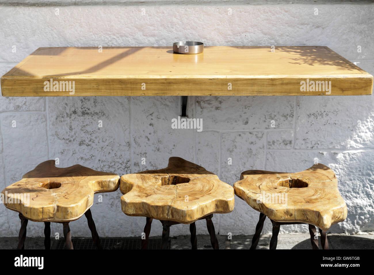 Tavolo bar con tre sgabelli in legno e muro bianco foto immagine