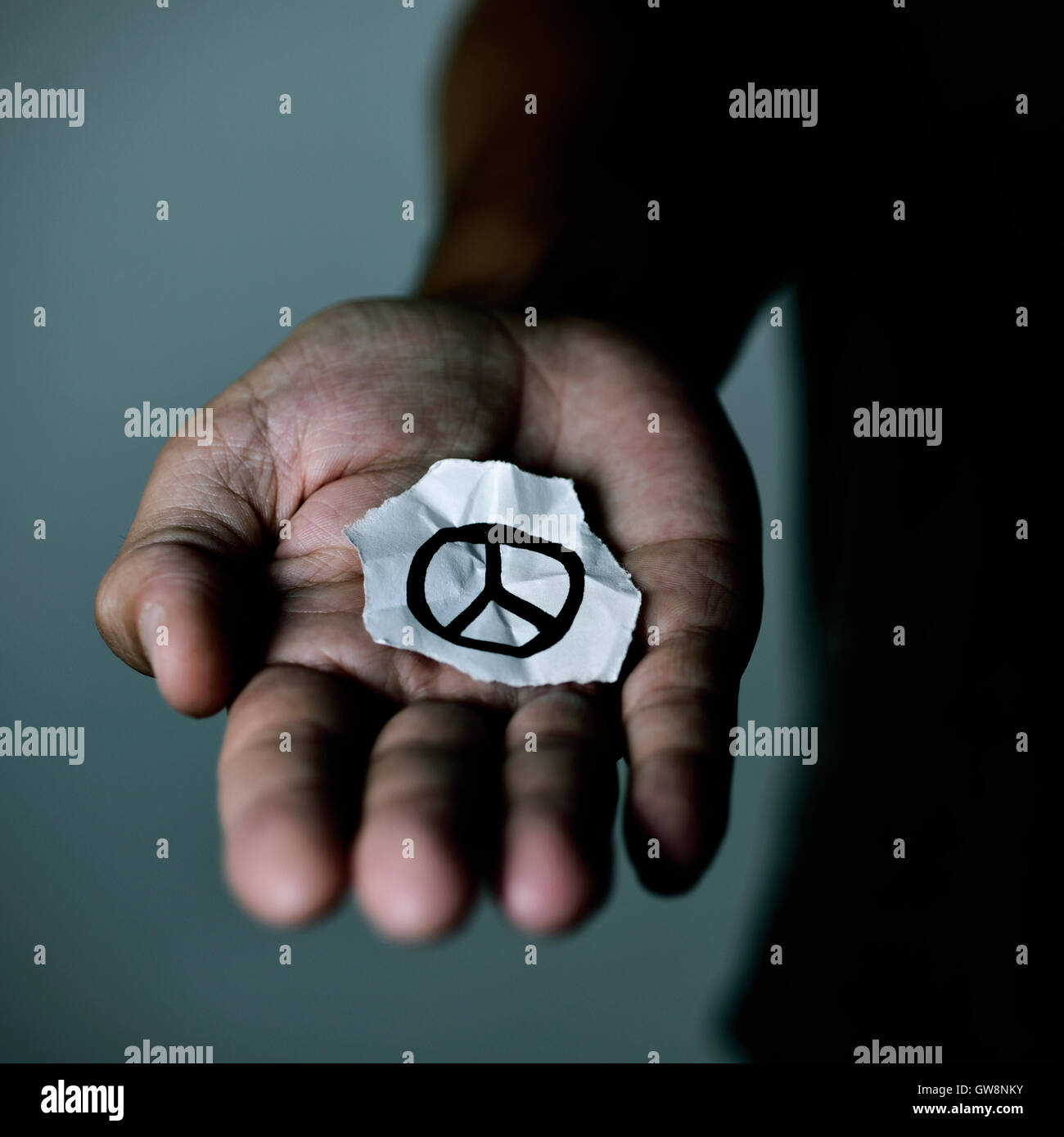 Primo piano di un giovane uomo con un pezzo di carta con un simbolo di pace tracciata in essa, nel palmo della mano Immagini Stock